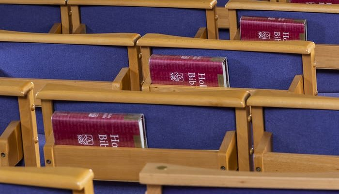 Rows of wooden church chairs with Bibles