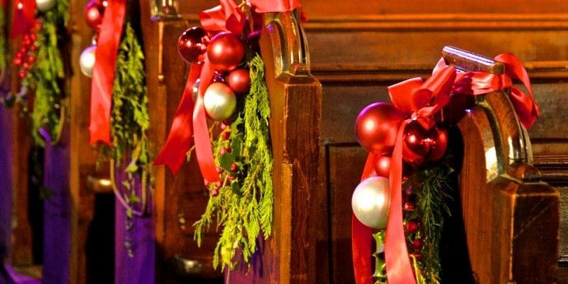 Church pews decorated with Christmas evergreens and red bows