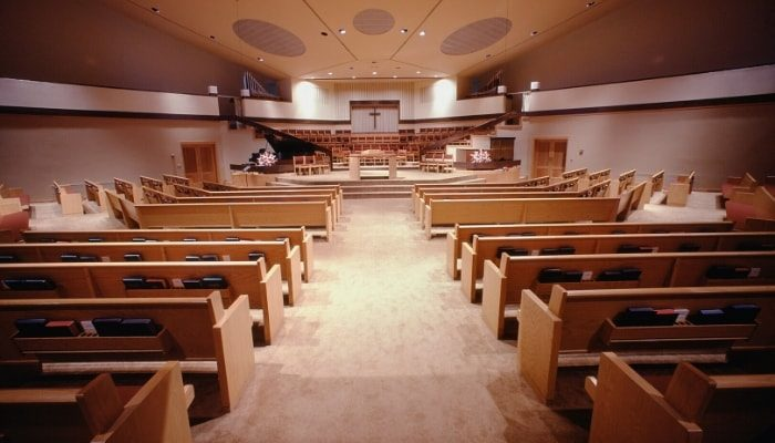 Interior of a church with wooden pews and beige carpeting and walls