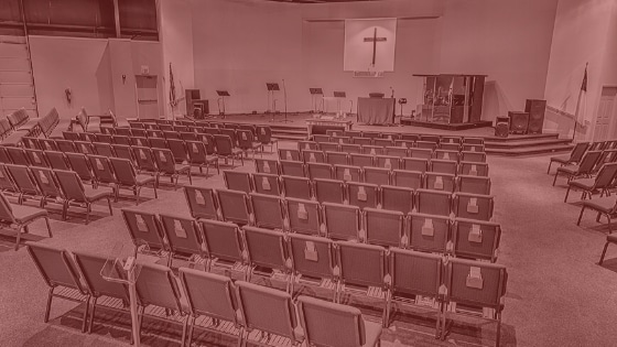 An image of rows of church chairs with a red tint
