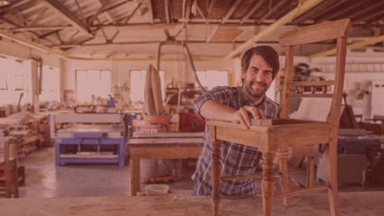 A man sands a wooden church chair frame
