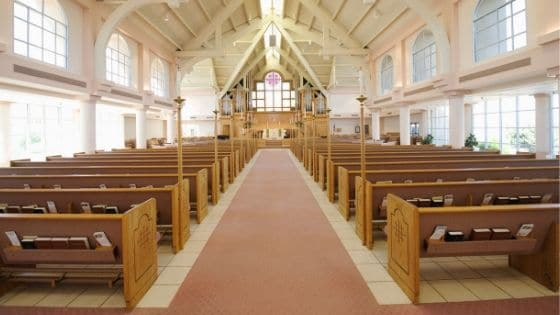 Interior of a church with white tile flooring, red carpet, wooden pews, and white walls