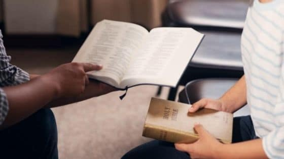 Two people meet for Bible study in a church multipurpose room