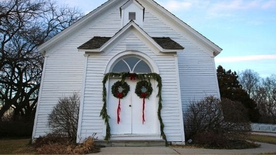 The exterior of a church decorated with evergreen wreaths for Christmas