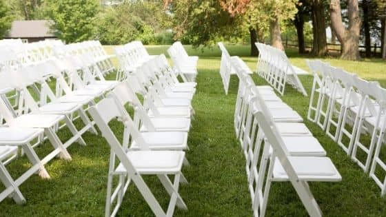 White folding chairs set up in rows for a wedding