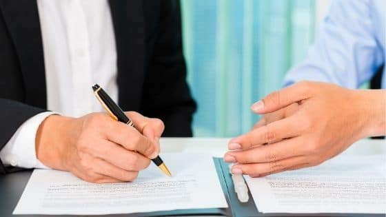 Two people discuss a rental agreement as a man signs the contract