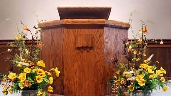 A wooden pulpit with yellow flowers on either side