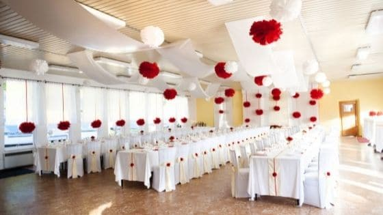 A wedding reception hall set up with rows of white tables and chairs